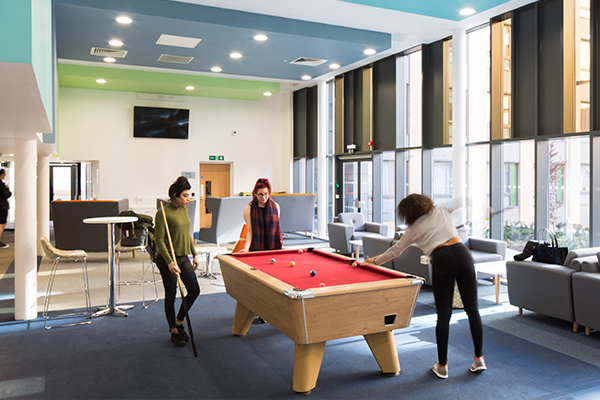 three students playing pool.