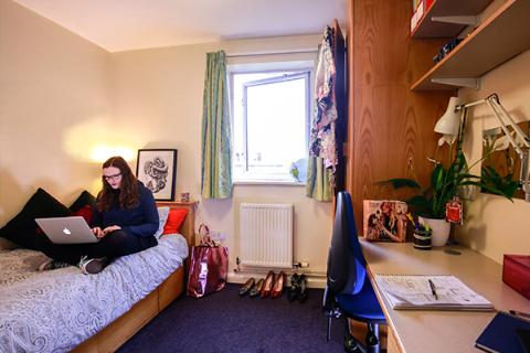 A student sat on her bed in a bedroom in Kirkstall Hall.