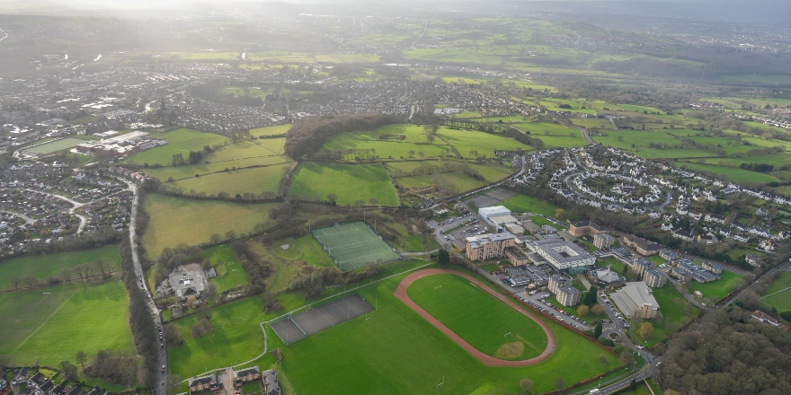Aerial image of green spaces, buildings, sports field.