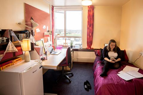 A student sat on her bed in a bedroom in Ripon Hall.