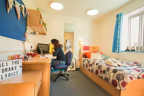 A student working at her desk in a bedroom in Trinity Close.